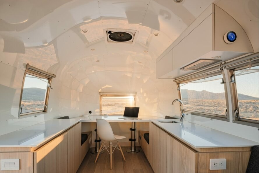 white interior of airstream trailer with wood cabinets and small desk