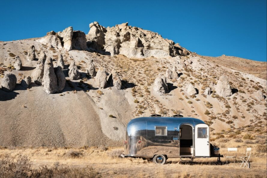 silver airstream trailer with door open near rocky mountain