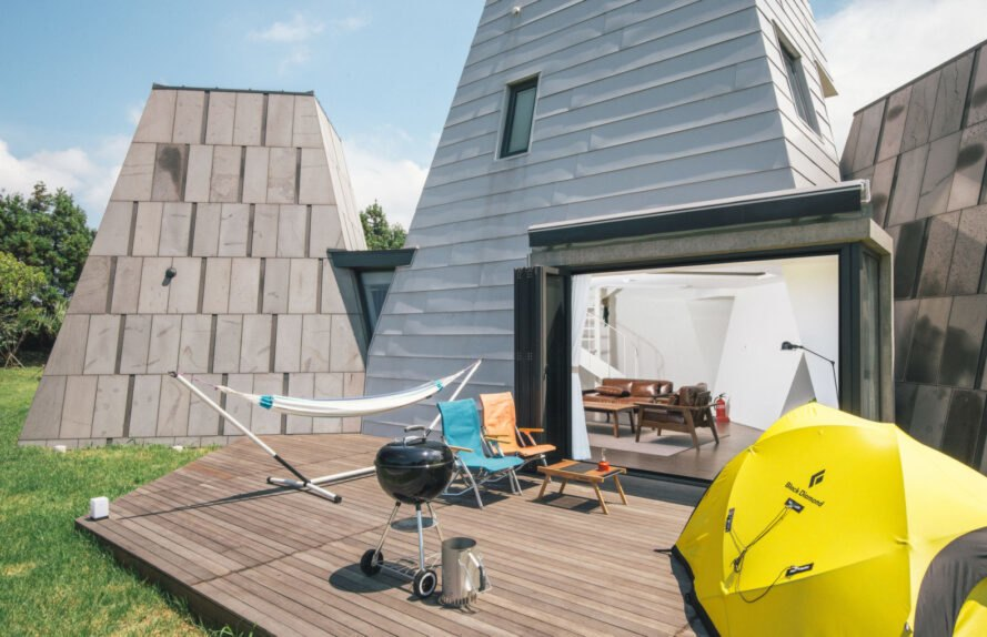 gray triangular structure with outdoor deck with a grill
