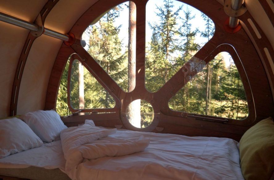 bed near windows with views of treetops
