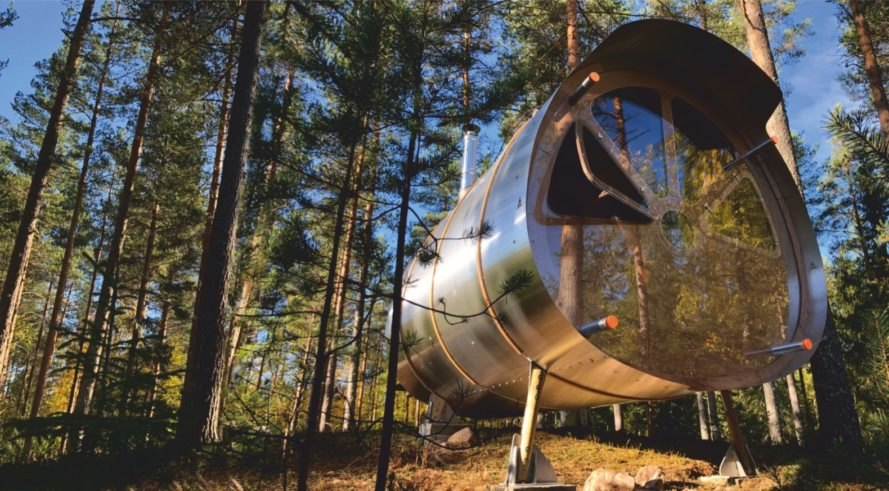 cylindrical timber and aluminum treehouse in a forest