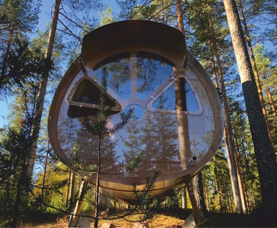 cylindrical timber and aluminum treehouse surrounded by trees