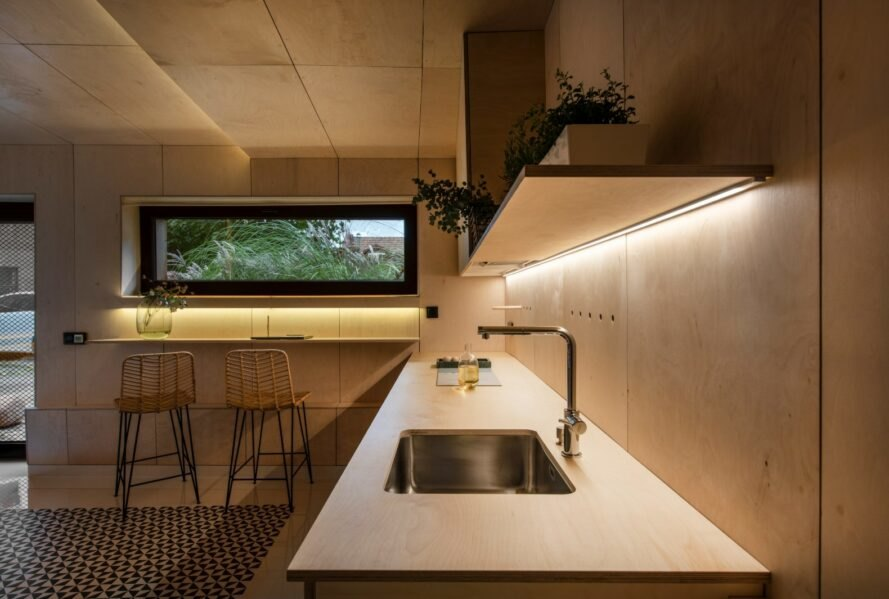 wood-lined kitchen with a metal sink and recessed lighting