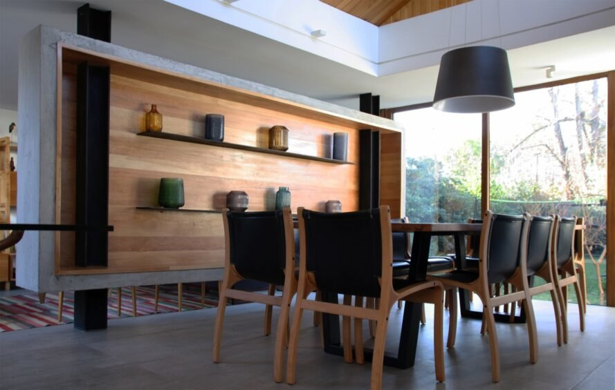 dining room with wood table and wood wall with floating shelves