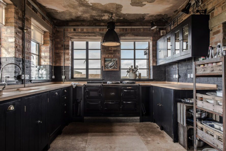 large kitchen with dark cabinets and windows