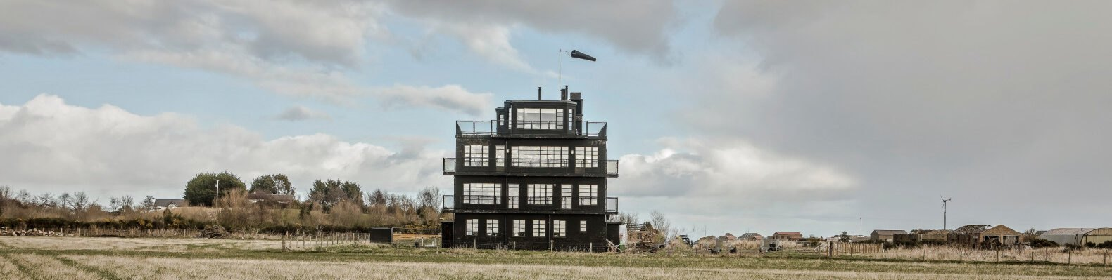 black air traffic control tower in a grassy field
