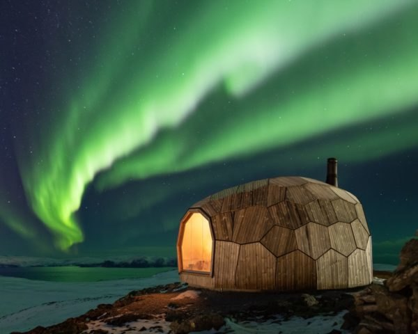 circular timber cabin on mountain top with northern lights in the background