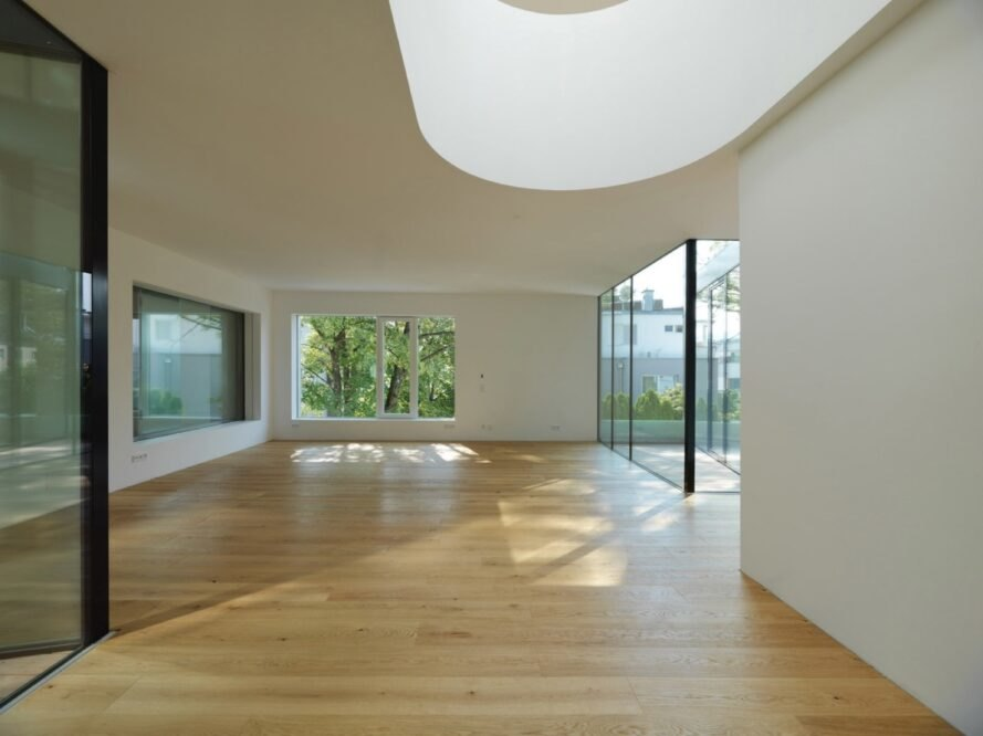 huge white room with wooden floors and curvy skylight