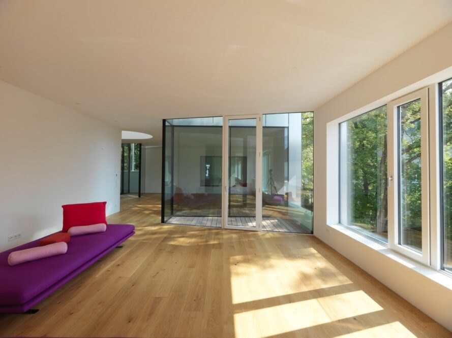 white room with wood floors and fuchsia couch