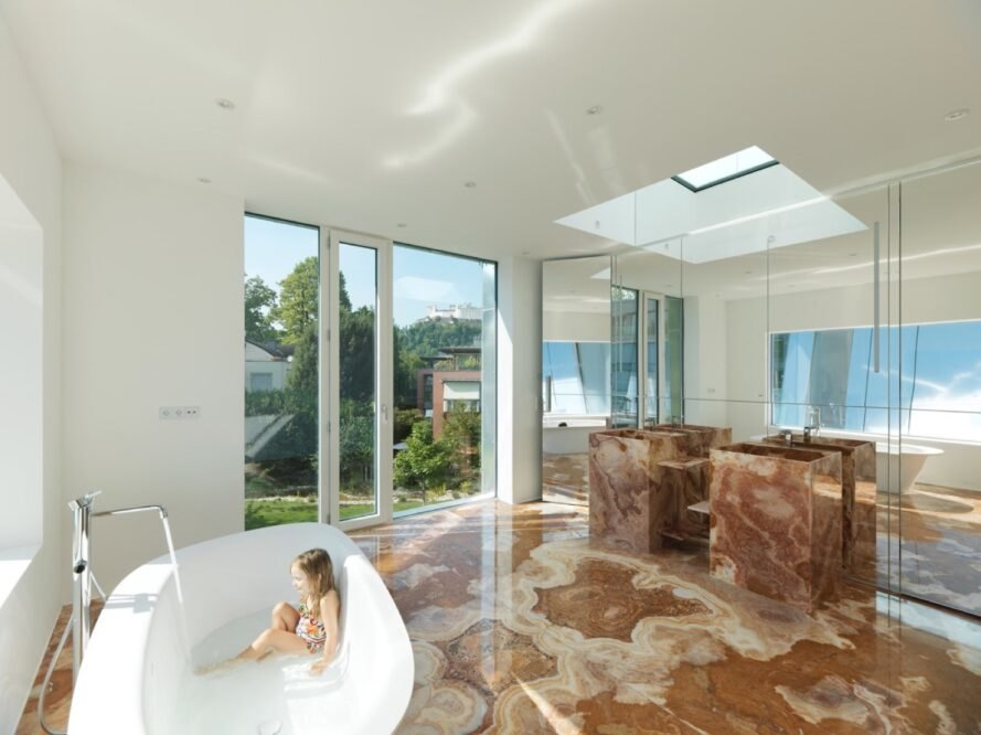 bathroom with brown marble floors and sinks and a white freestanding tub