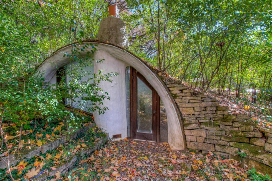 curved hobbit house with green roof