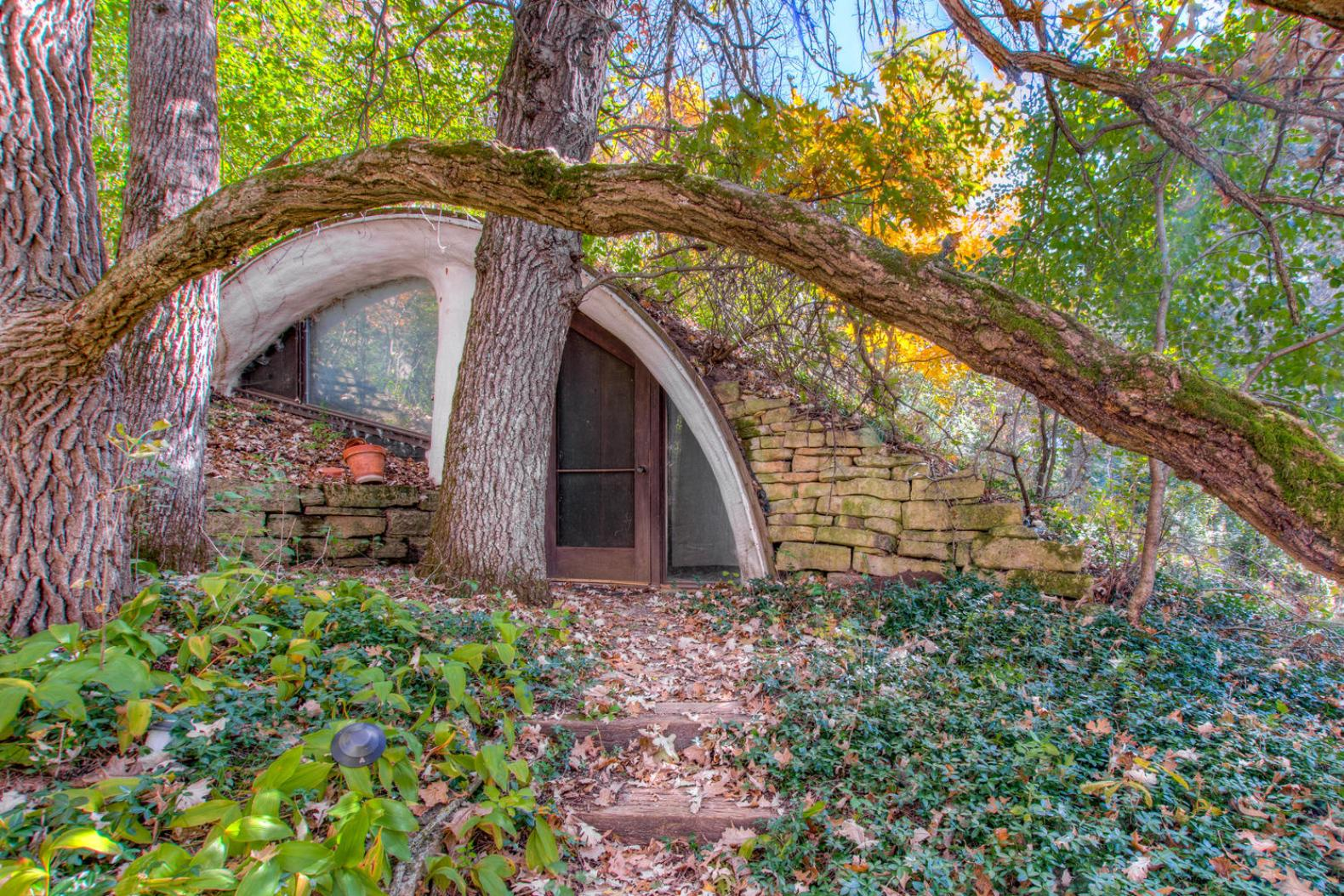An earth-bermed hobbit house with two glass arches hits the market for $190,000