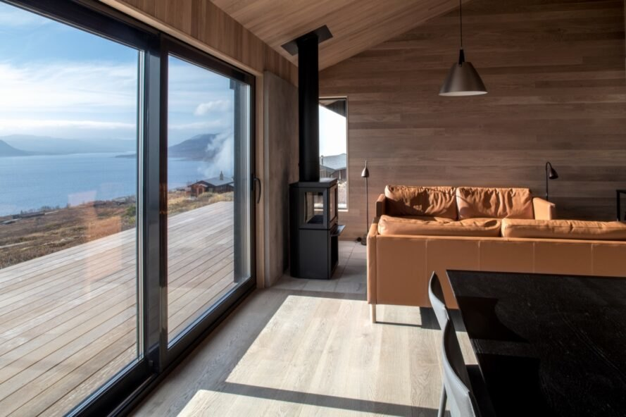 tan leather couches and wood-burning stove near large glass window