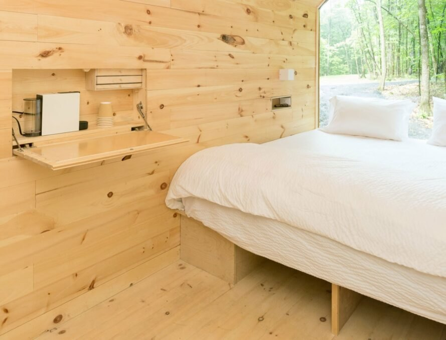 bed with all-white linens in small cabin