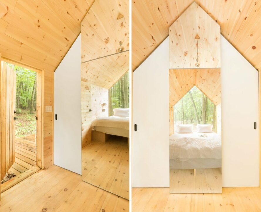 interior of tiny cabin with large glazed wall and wood walls, ceilings and floors