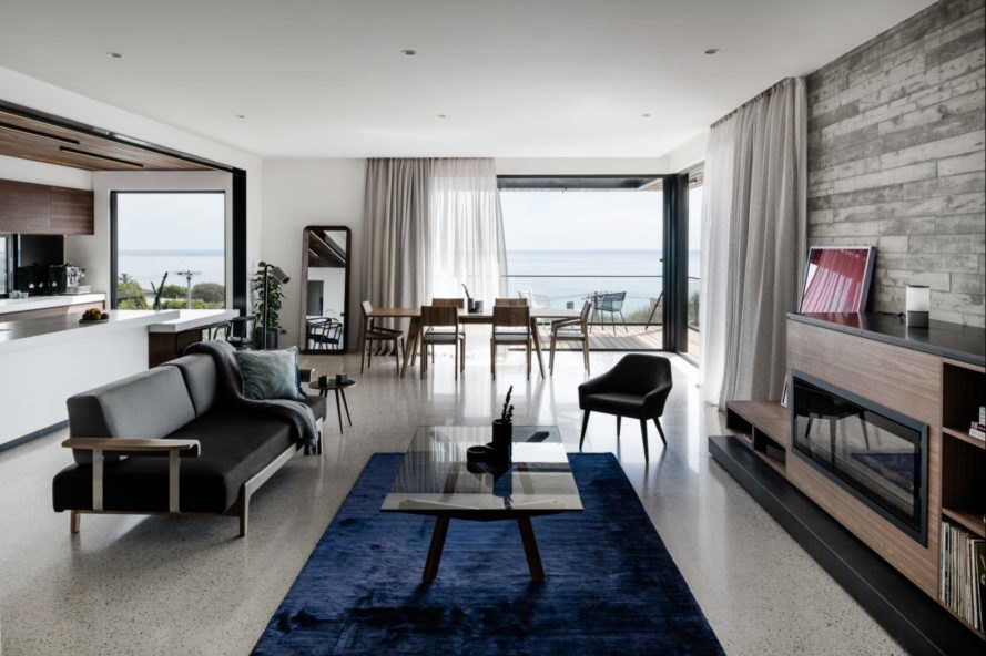 living room with blue rug, gray sofa, and glass wall revealing sea views