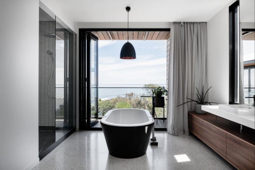 black bathtub in middle of bathroom with view of the sea