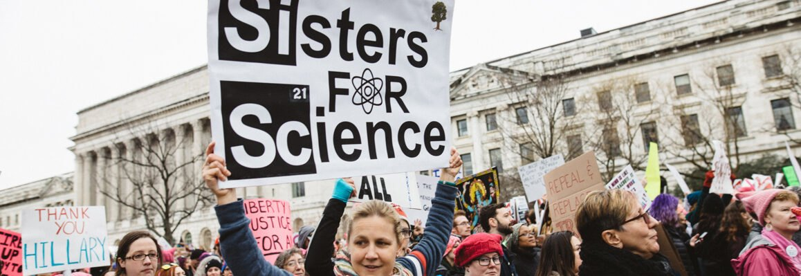 Women holding sisters for science protest sign during a rally
