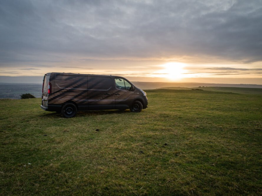 long dark van on expansive green land