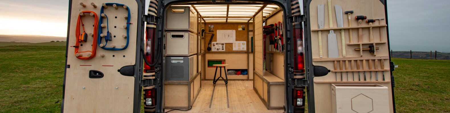 back of van with doors open to reveal woodworking shop