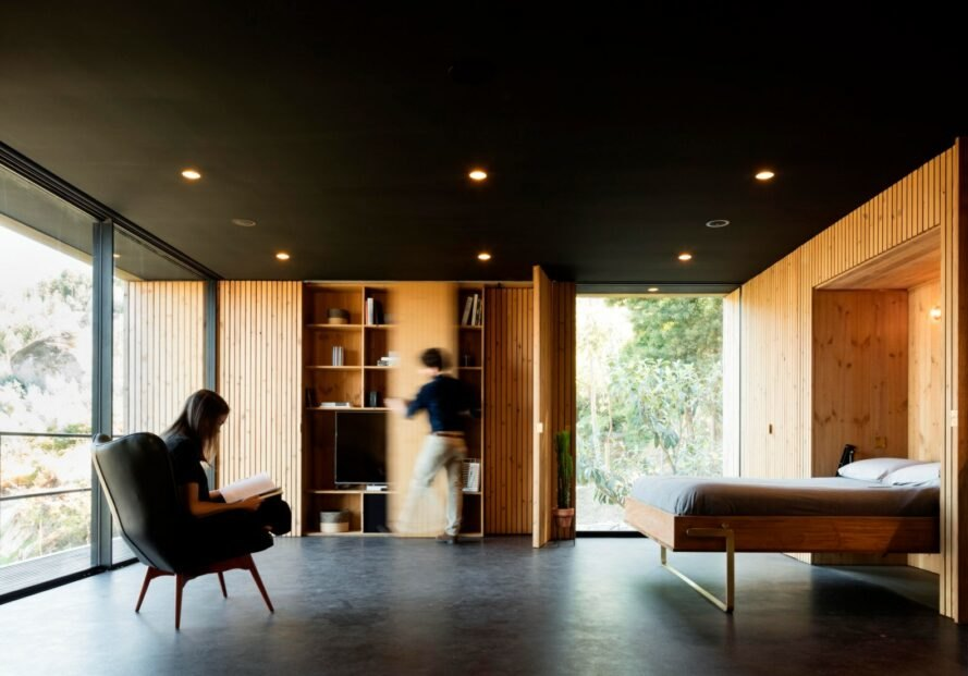 interior living space with black ceiling and timber walls