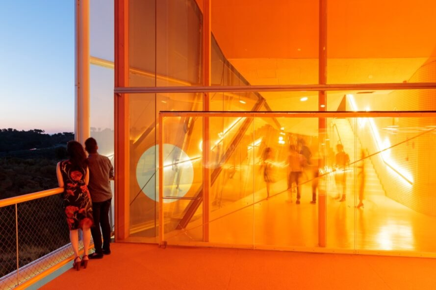 people standing outside a room with transparent orange walls