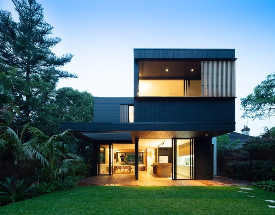 black two-story home with large patio all lit up at dusk