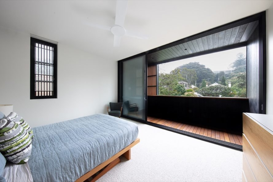 bedroom with gray bed facing a balcony