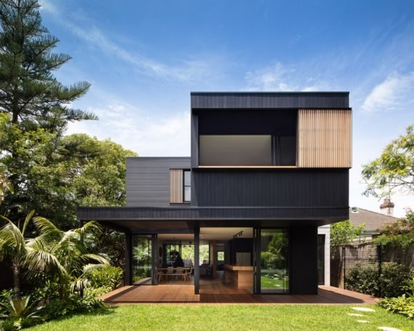 black two-story home with large patio