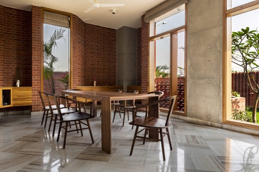 dining are with wood table and chairs along with wood accentuated floor to ceiling windows