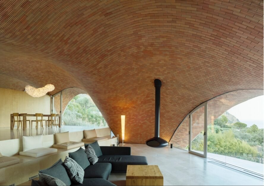 An interior living space with arched ceiling and curved windows