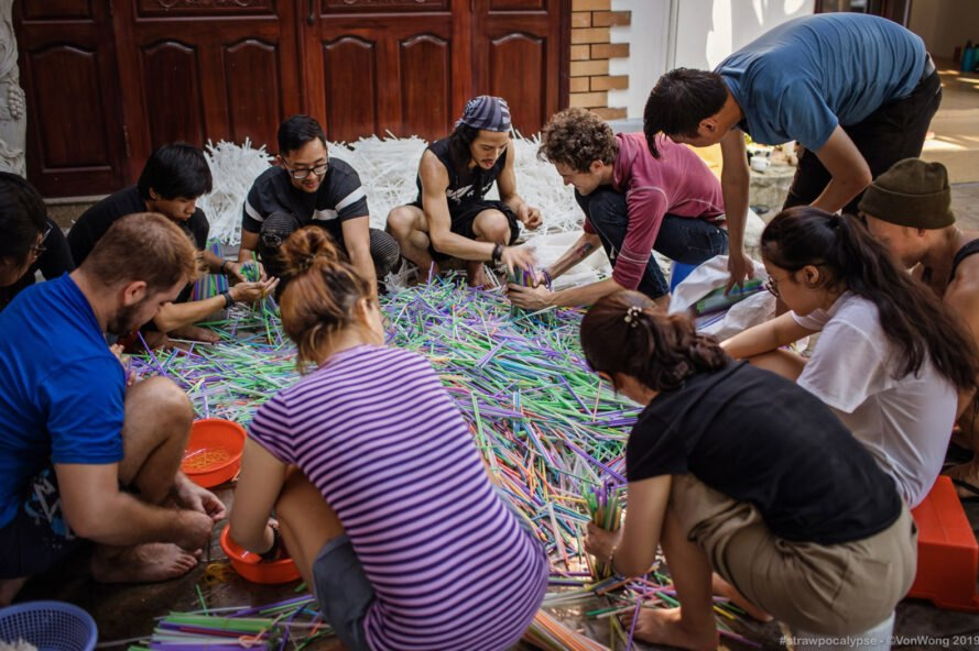 artist Von Wong and helpers sort through thousands of plastic straws for the art installation