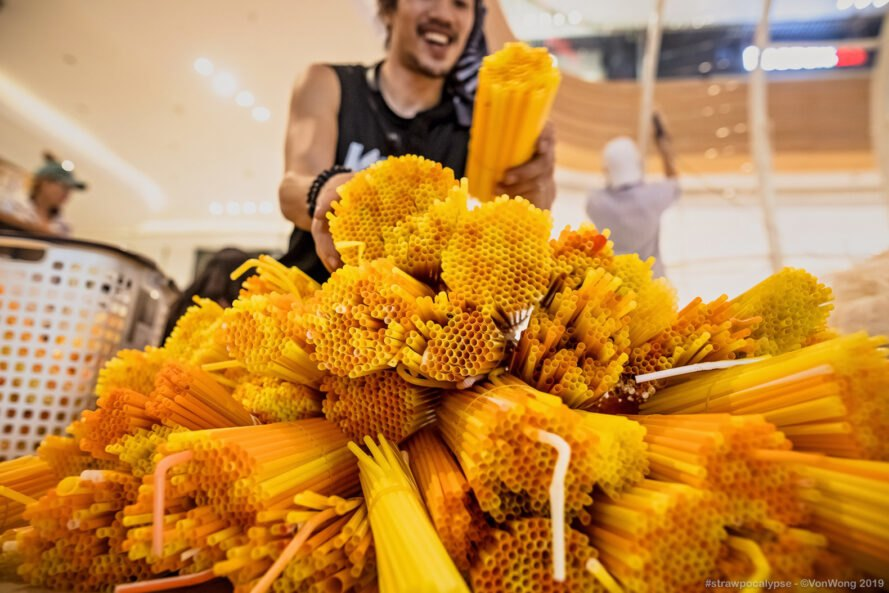 artist Von Wong collecting yellow plastic straws for the installation