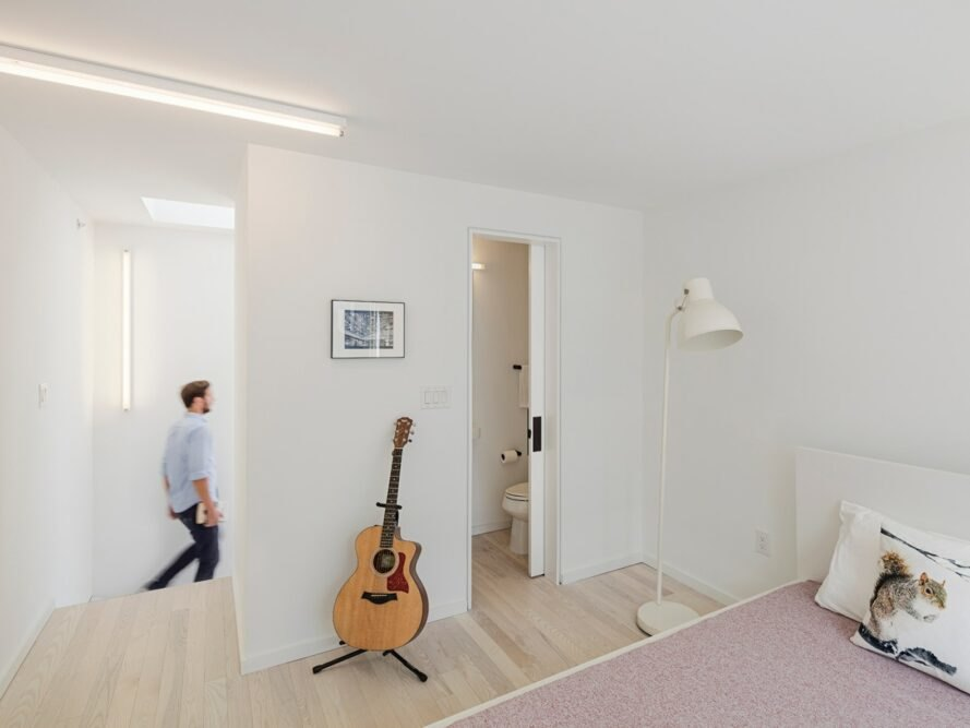 man walking past white room with bed and guitar