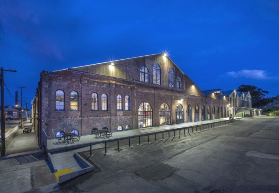 huge brick building with gabled roof lit up at night