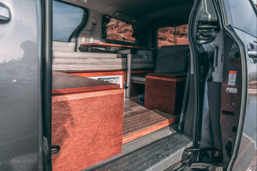 dark camper van with side door open, revealing living space inside