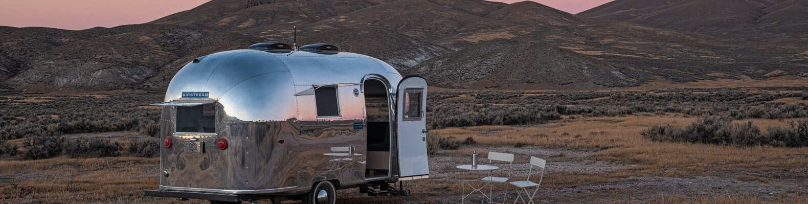 silver airstream trailer with door open at sunset
