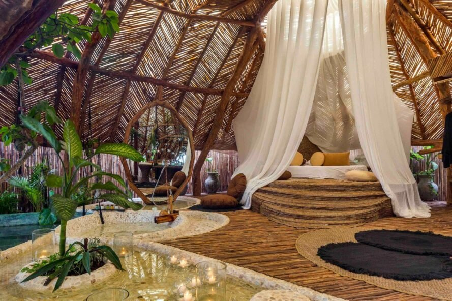 wood room with thatched roof and canopy bed