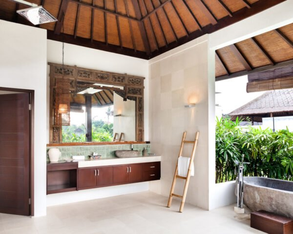 bathroom with wood cabinets, plants and a stone freestanding tub