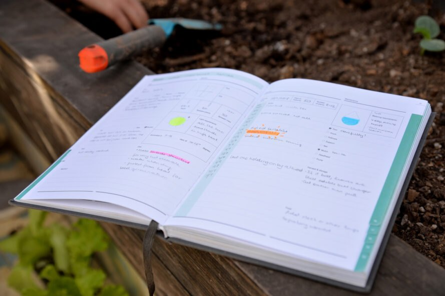 open notebook with highlights beside a garden