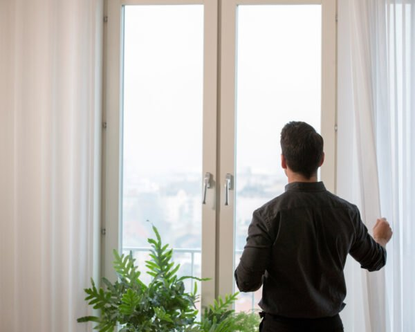 man standing by window with white curtains