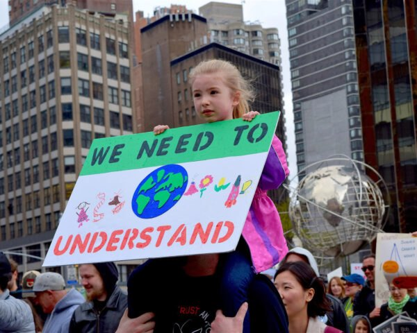 little girl holding environmental poster sign during rally