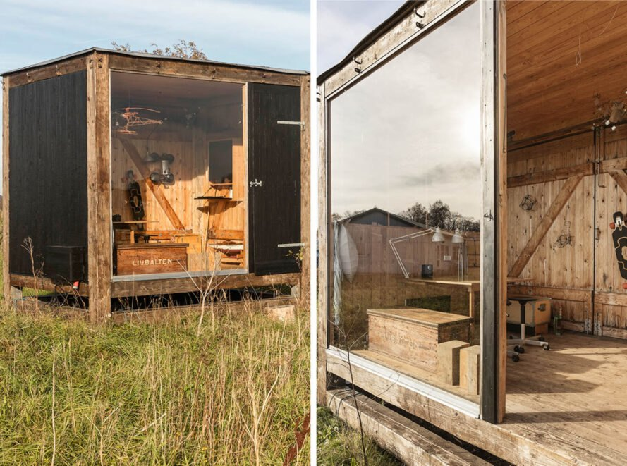 small wooden cube studio with glass wall in a grassy field
