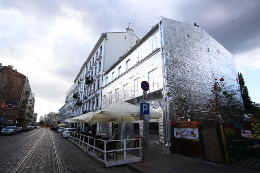 angled photo of gabled building wrapped in foil