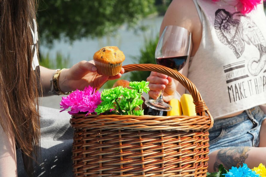 two people grabbing muffins and wine from a picnic basket