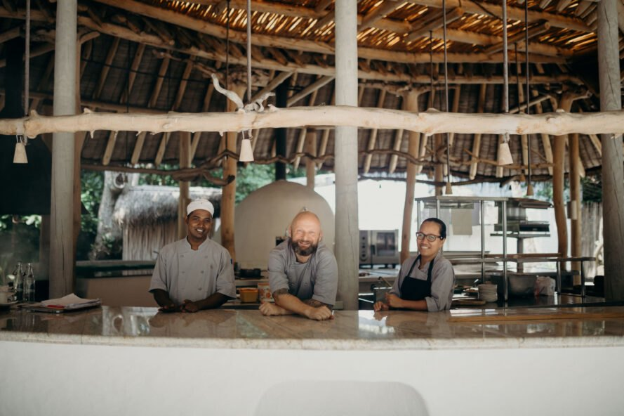 chefs standing at bar under hut with thatched roof