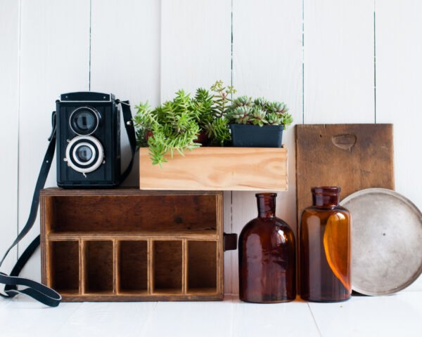vintage black camera atop of wood box with plants and brown glass bottles