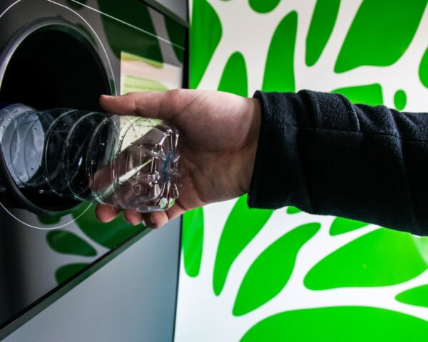 Person using a bottle drop automated recycling machine