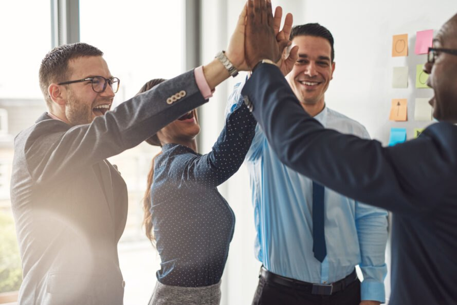 group of colleagues high five each other