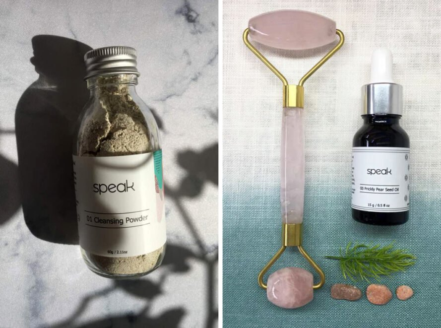 On the left, glass jar of cleansing powder. On the right, rose quartz roller and small vial of prickly pear seed oil.